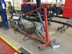 Mechanic takes engine off frame.